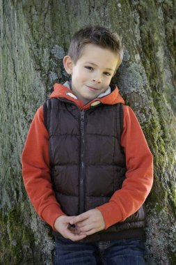 shy young boy leaning against a tree