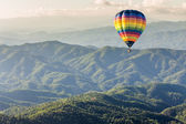 Fotografia aerostato di aria calda sopra la montagna