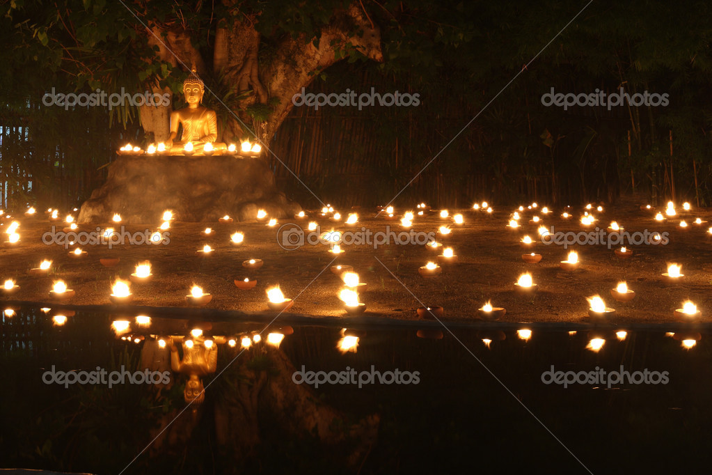 Statua di buddha si riflettono sull acqua con fuoco candele di