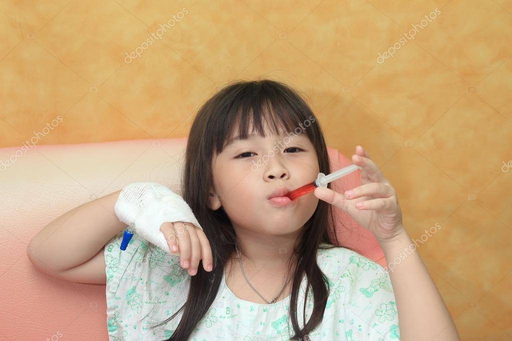 Little girl drinking syrup with syringe.