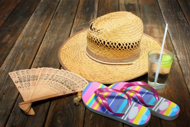 Straw hat, flip flops and cold drink on wooden background