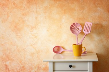 Kitchen cooking utensils. plastic spatulas in yellow cup against rustic terracotta wall.