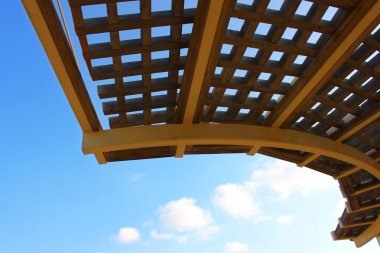 Close-up of a wooden garden pergola with blue sky in the background