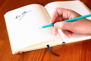 Woman hand holding pencil and opened notebook with a to do list.