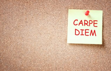 Sticky note pinned to corckboard with the phrase carpe diem. room for text.