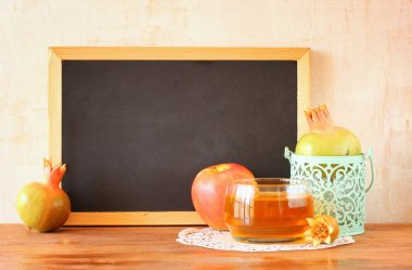 Empty blackboard, apple, honey and pomegranate. rosh hshanah concept.