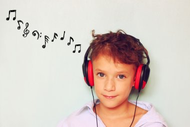 Cute kid  (girl) with headphones having fun listening to music,  and notes sketches.