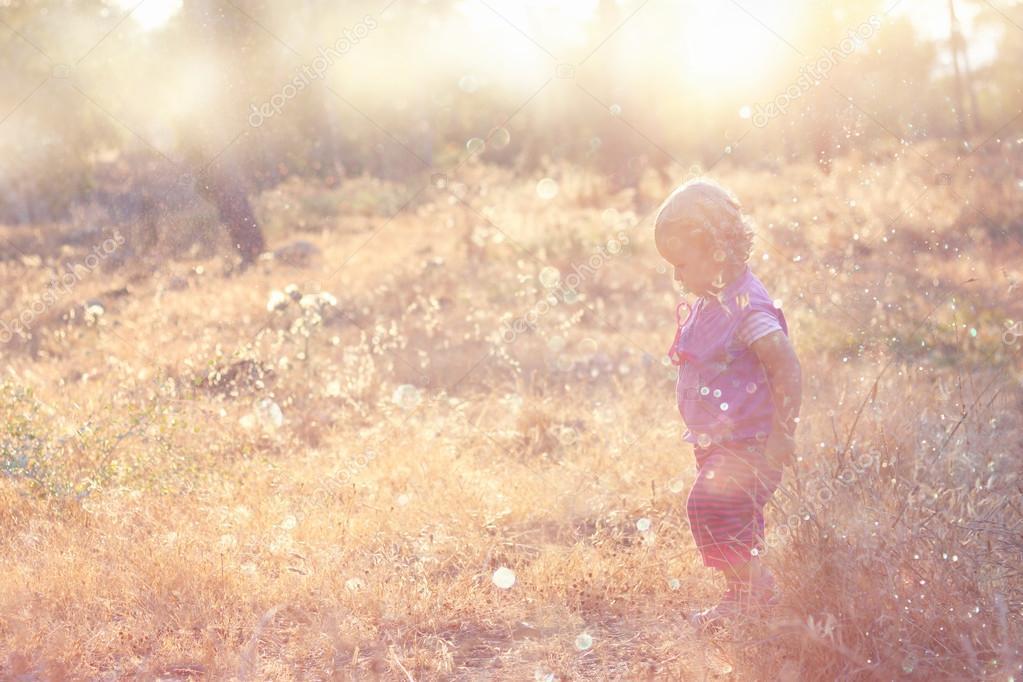 Cute kid walking in field and warm sunset light.