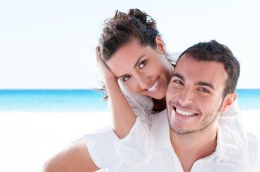 Smiling young couple piggyback at beautiful summer beach stock vector