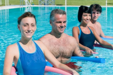 Smiling fitness exercising in swimming pool