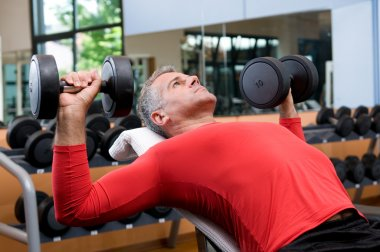 Exercising with dumbells at gym