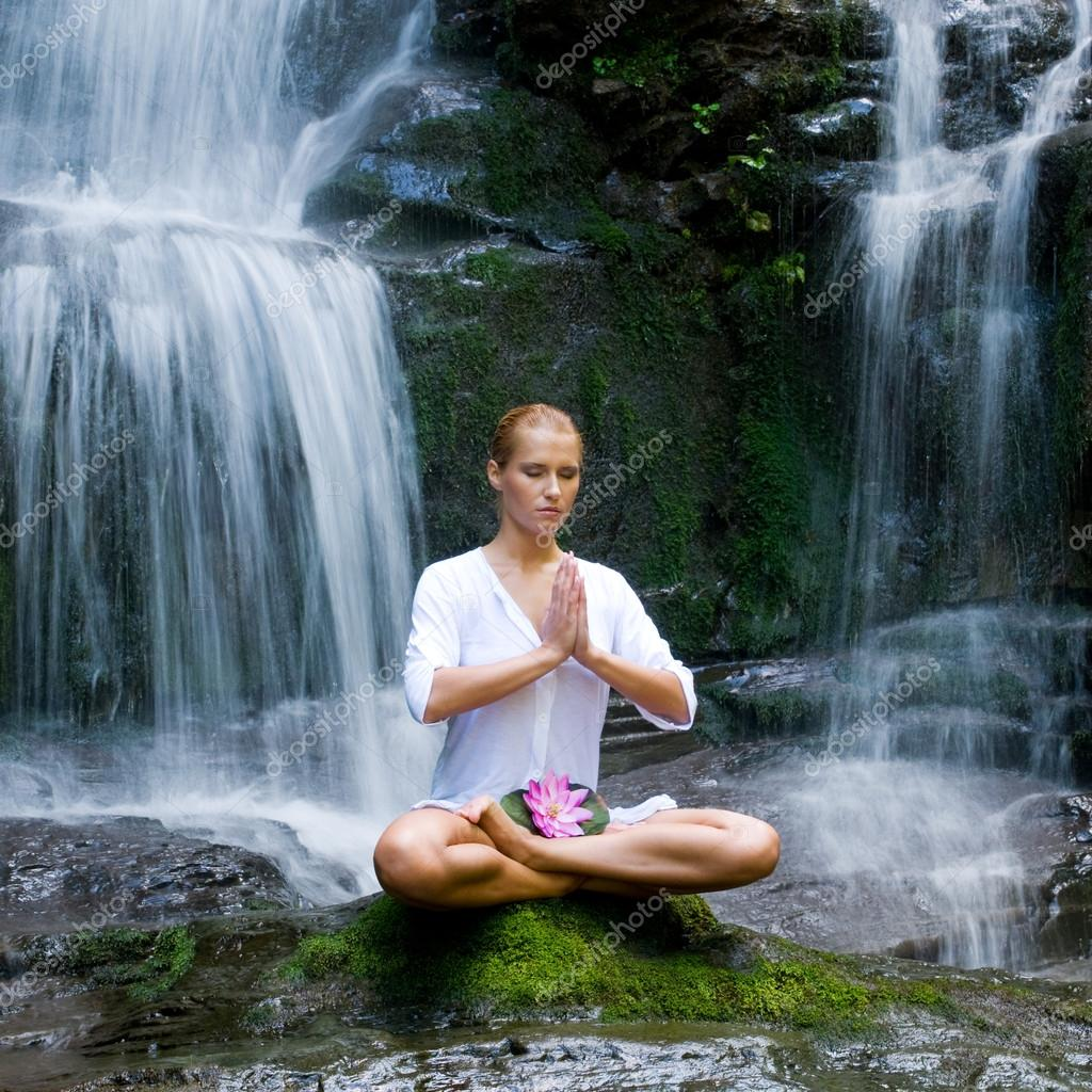 Young woman doing yoga near waterfalls