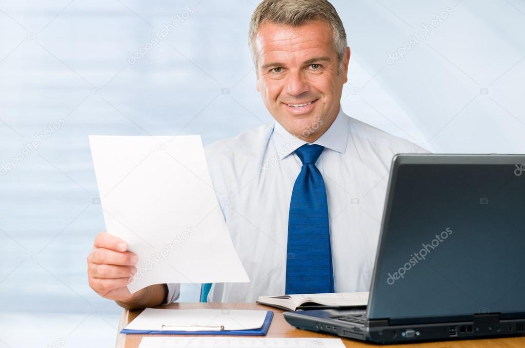 Mature positive businessman holding paperwork and looking at camera smiling
