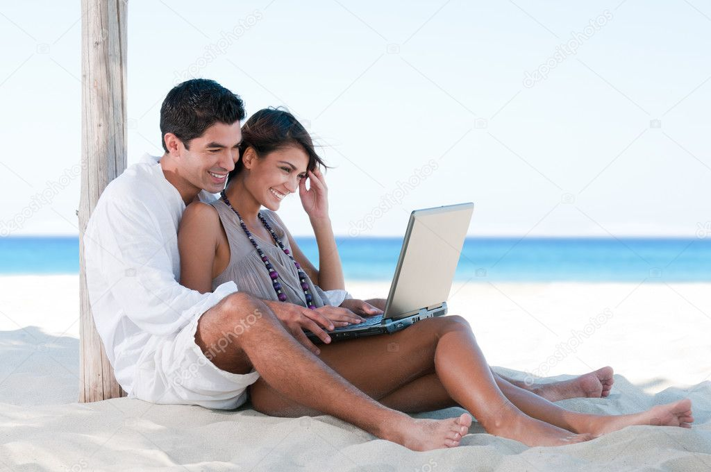 Summer couple using laptop