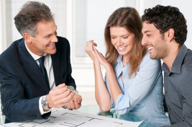Happy estate agent showing new home keys to a young couple after a discussion on house plans. stock vector