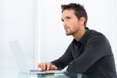 Thoughtful Businessman Working On Laptop