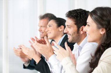 Happy business team clapping hands