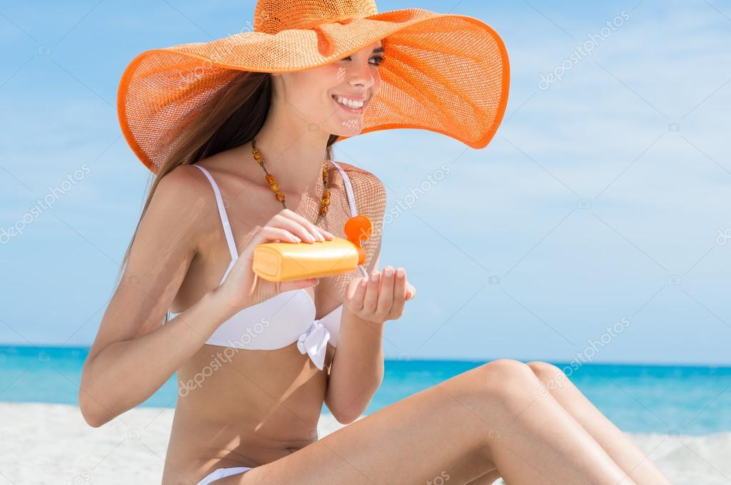 Smiling Girl At Beach Applying Sun Protection Cream