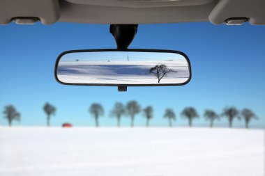 Snow landscape reflected in the car rear view mirror
