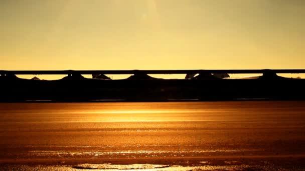 siluety aut na dálnici. západ slunce
