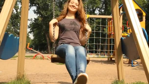 Young girl swinging on a swing in the park
