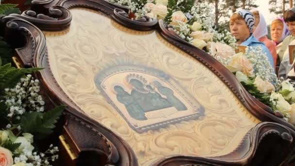 Ancient icon in a wooden frame surrounded by flowers