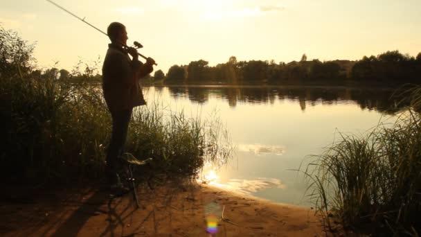 Muž, rybaření. rybář. západ slunce na jezeře. letní krajina