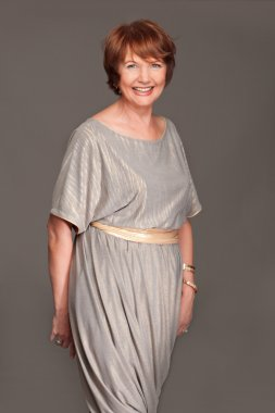 Happy beautiful fashionable mature woman in grey dress. Studio s