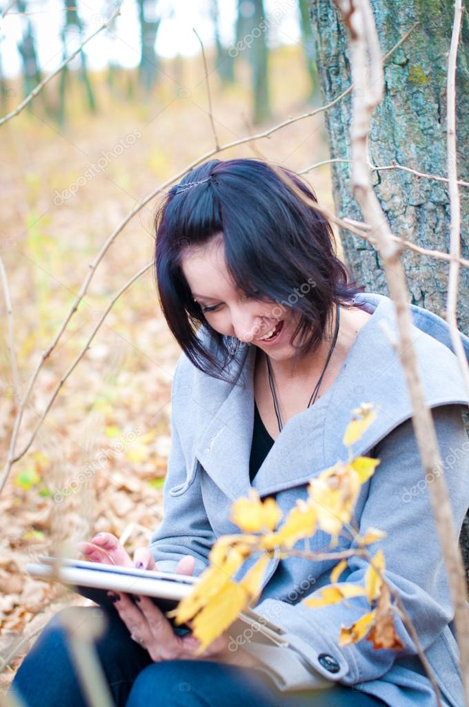 Woman in the forest with tablet-pc