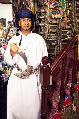 Knives seller on Muscat market shows his traditional Omani knife