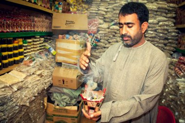 Incense man burning myrrh (mira) on market, suk, in Muscat, Oman