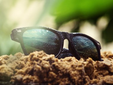 Sunglasses are covered with rain drops are on the wet sand