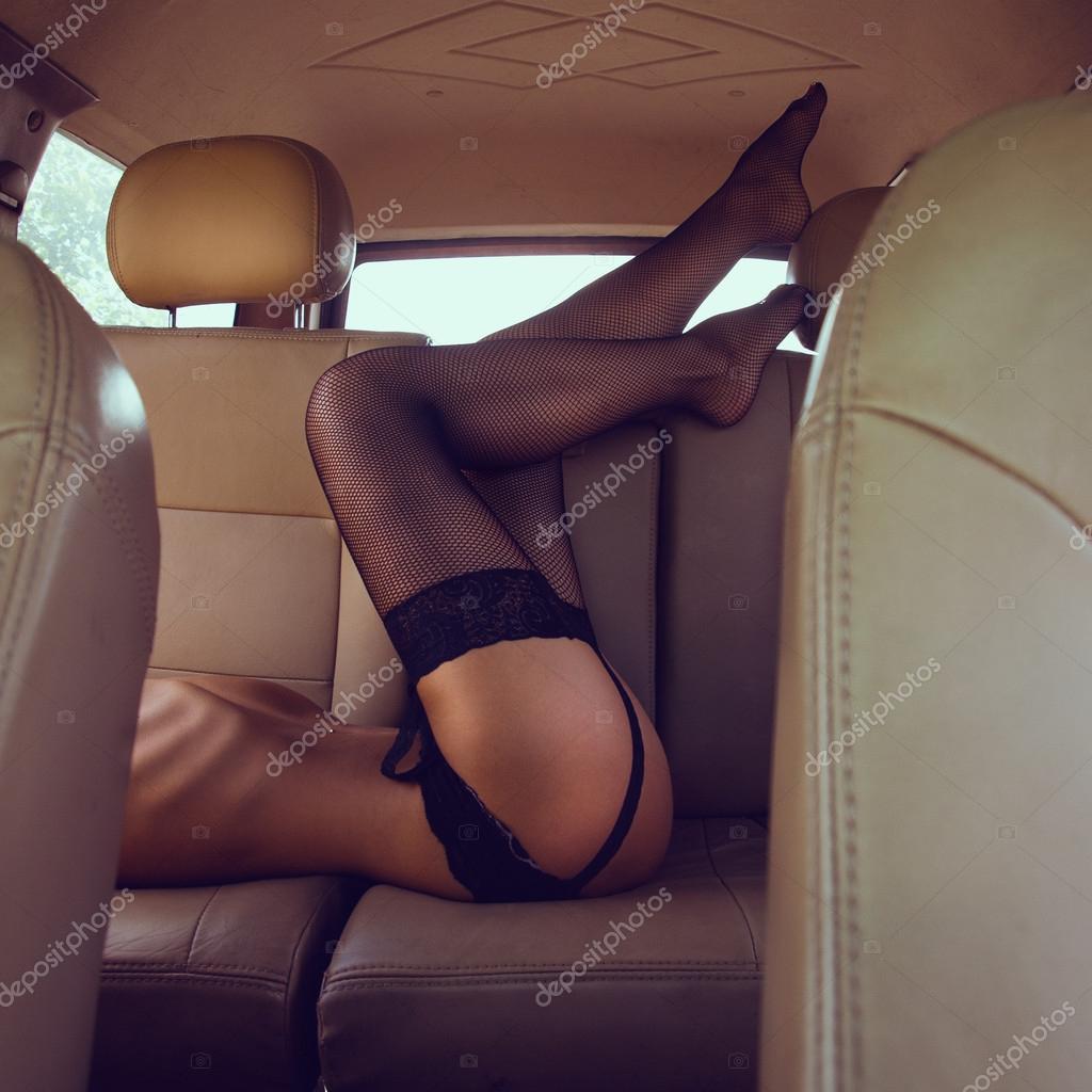 Sexy woman lying in backseat of car