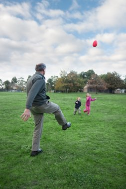 Kids playing sport with grandfather