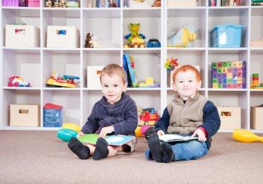 Smiling children reading kids books in play room