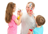 Fotografie Familie mit Kindern malt mit Pinsel auf Papa