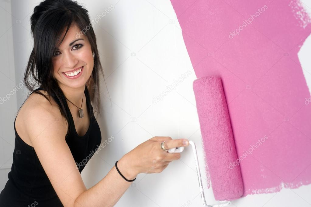 a brunette woman paints the wall of her apartment photo by cboswell - Woman Home Decorating