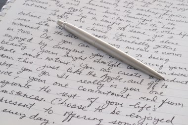 Stainless Steel Pen Laying on Written Page