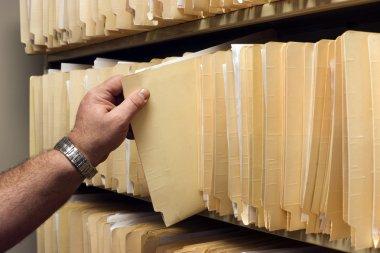 Human Hand Pulls File Folder off Shelf of Client Files