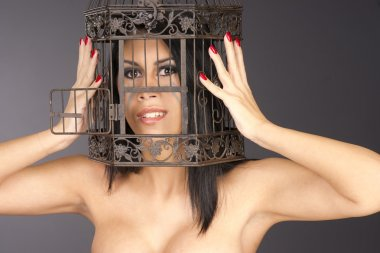 Beautiful Manicured Woman Holding Her Head Inside Metal Bird Cag