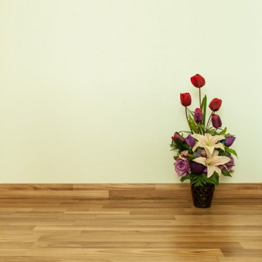 Artificial Flowers on Parquet Flooring in room.