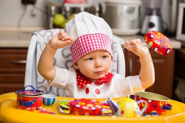 Baby cook girl wearing chef hat in kitchen.  Use it for a child, healthy food concept
