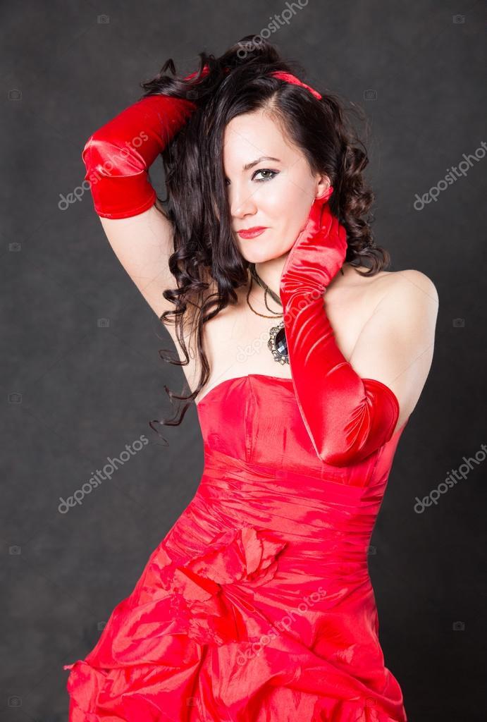 4f99faa5109d43 Mooie brunette vrouw met lange haren in rode satijnen jurk op grijze  achtergrond — Foto van ...