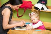 Matka a dítě dívka kreslení jakož i barevné tužky v mateřské školce u stolu v mateřské školce