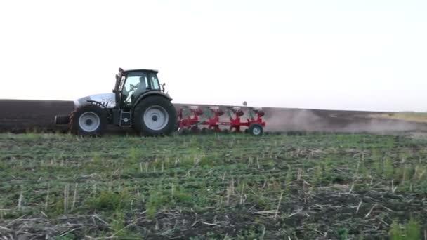 traktor orat pole při západu slunce