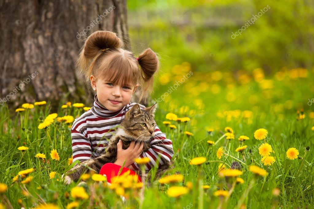 Little girl playing with a cat in the park