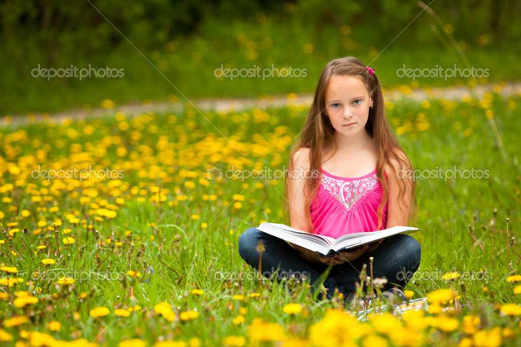 Girl (looking at the camera) reads a book in the meadow