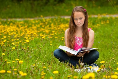 A girl 11 years old reads a book in the meadow