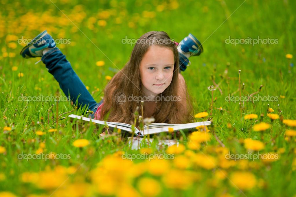 ein mädchen 11 jahre alt liest ein buch auf der wiese