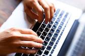 Fotografie Hände, die auf Computer-Tastatur eingeben